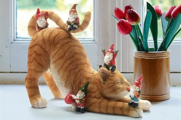 Gatto con gnomi da giardino